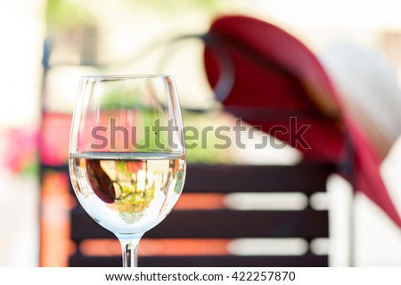 Glass of delicious fresh white wine on wooden table on summer terrace. Colorful outdoors horizontal image. - stock photo