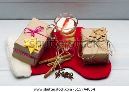 Glass of delicious glintwein or mulled hot wine, cinnamon, thread, anise, gifts wrapped in craft paper with bow and with Santa Claus red sock on vintage wooden background