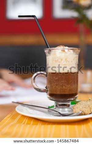 Glass of delicious iced coffee standing on a restaurant or coffee house counter topped with rich creamy vanilla ice cream - stock photo