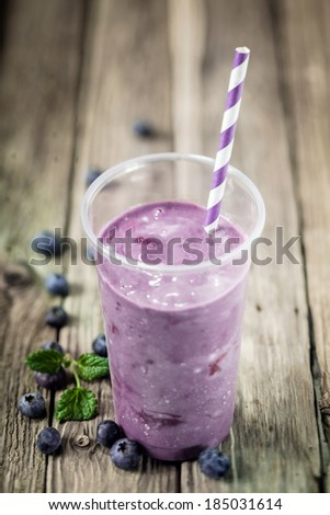 Glass of delicious purple healthy blueberry smoothie blended with ice cream or yogurt with fresh fruit on rustic wooden boards with copyspace - stock photo