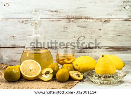 Glass of drink and carafe of alcohol tincture with quince fruits. - stock photo