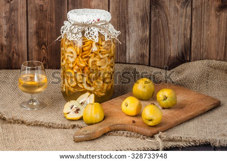 Glass of drink and jar of alcohol tincture with cutted quince fruits on a wooden background. - stock photo