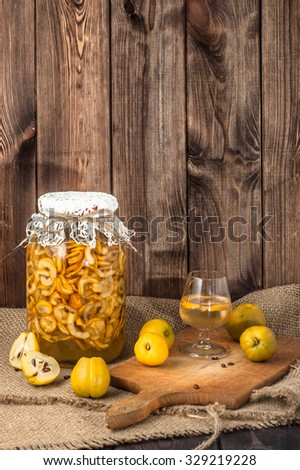 Glass of drink and jar of sliced quince fruits. - stock photo