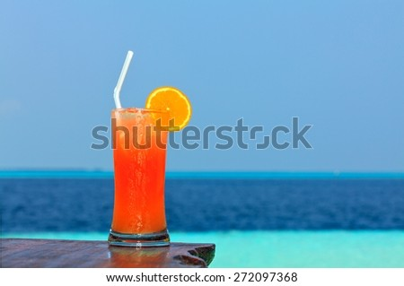 Glass of drink is on a beach table (Maldives, The Indian Ocean) - stock photo