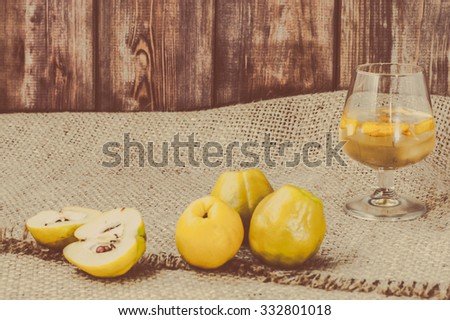 Glass of drink with quince fruits, vintage photo. - stock photo