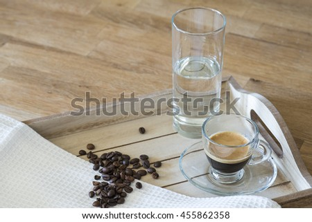 Glass of espresso, a glass of water and coffee beans on a wooden tray