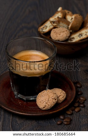 glass of espresso and almond cookies on dark background, vertical, close-up - stock photo