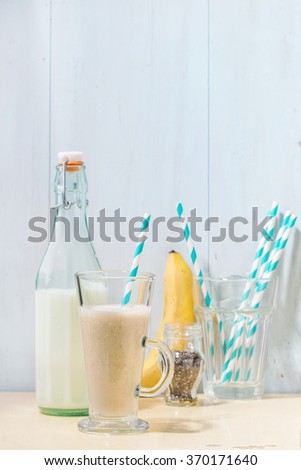 Glass of fresh Banana smoothie with retro cocktail tube, served with bottle of milk, banana and chia seeds over white wooden table. Rustic style - stock photo