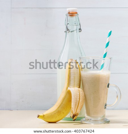 Glass of fresh Banana smoothie with retro cocktail tube, served with bottle of milk, banana and half of lemon over white wooden table. Square image - stock photo