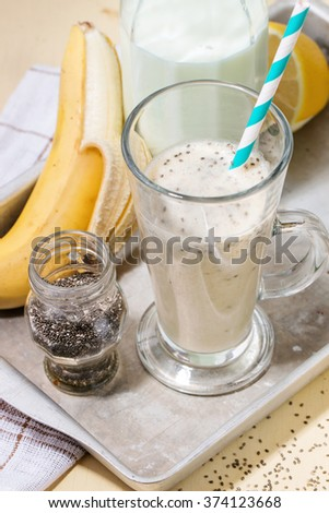 Glass of fresh Banana smoothie with retro cocktail tube, served with bottle of milk, open banana, jar of chia seeds and half of lemon on aluminum tray over white wooden table. Rustic style - stock photo