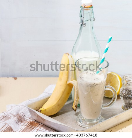 Glass of fresh Banana smoothie with retro cocktail tube, served with bottle of milk, open banana, jar of chia seeds and half of lemon on aluminum tray over white wooden table. Square image - stock photo