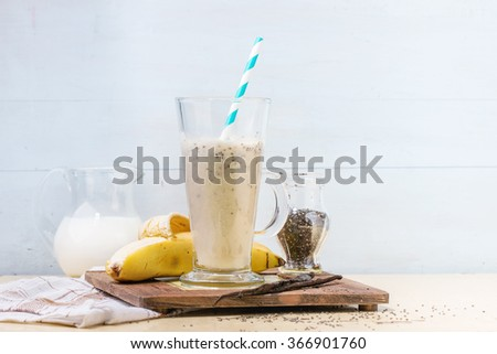 Glass of fresh Banana smoothie with retro cocktail tube, served with jug of milk, open banana, jar of chia seeds, vanilla and half of lemon on decorative board over white wooden table. Rustic style - stock photo