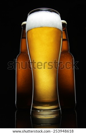 Glass of fresh beer on a black background  - stock photo