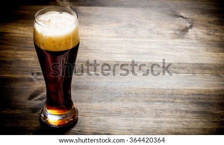 Glass of fresh beer on a wooden table. - stock photo