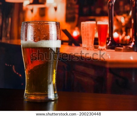 Glass of fresh beer on wood table in a pub - stock photo