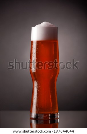 Glass of fresh beer with cap of foam