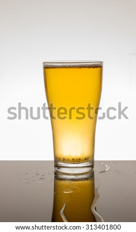 Glass of fresh beer with cap of foam isolated on white background - stock photo