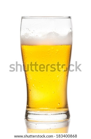 glass of fresh beer with drops on white background, with reflection on table - stock photo