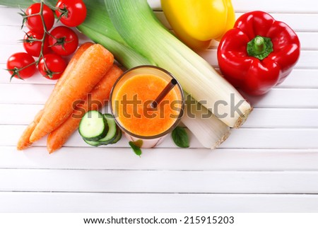 Glass of fresh carrot juice and vegetables on wooden background