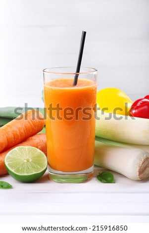 Glass of fresh carrot juice and vegetables on wooden table