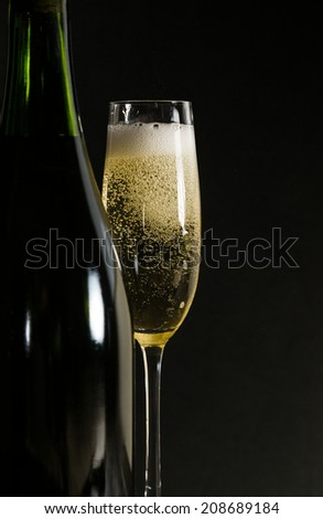 Glass of fresh champagne with black background - stock photo