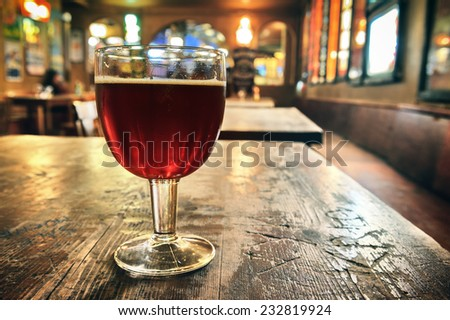Glass of fresh dark beer on rustic pub background - stock photo