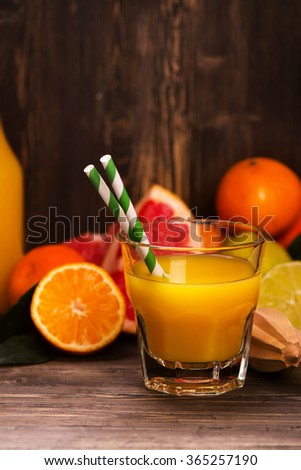 Glass of fresh homemade orange juice with pile of fruits over grunge wooden background. Selective focus - stock photo