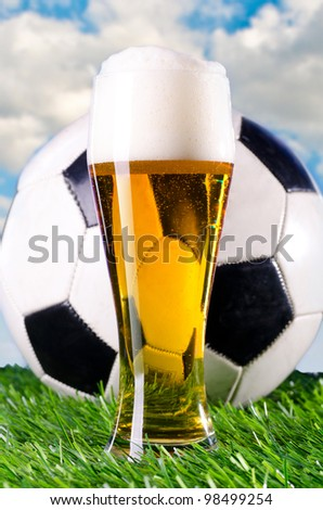 glass of fresh lager beer and ball against cloudy skies - stock photo