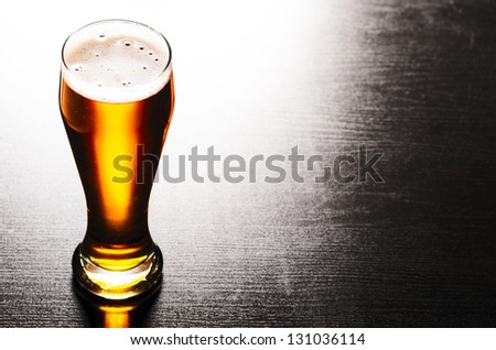glass of fresh lager beer on black table - stock photo