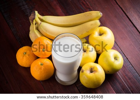 Glass of fresh milk and fruits on wooden background - stock photo