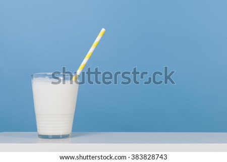 Glass of fresh milk with drinking straw