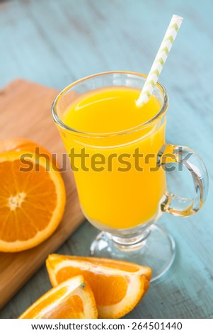Glass of fresh orange juice breakfast beverage with a straw vertical - stock photo