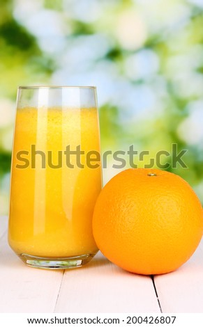 Glass of fresh orange juice on wooden table, on green background