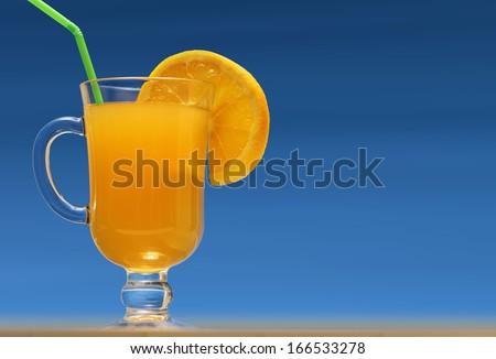 Glass of fresh orange juice with lemon slice and green drinking straw on blue background - stock photo