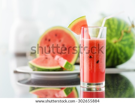 Glass of fresh red watermelon juice on table in kitchen. Ripe watermelons and slices in background. Healthy eco sweet food rich in vitamins. Popular product of organic farming. - stock photo