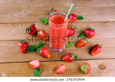 Glass of fresh strawberry juice on wooden background - stock photo