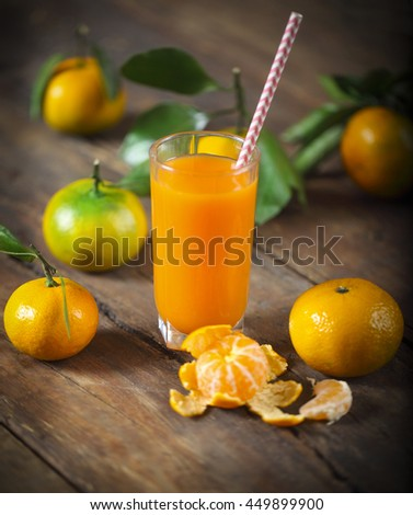 Glass of fresh tangerine juice with ripe tangerines, leaves and old-fashioned straw - stock photo