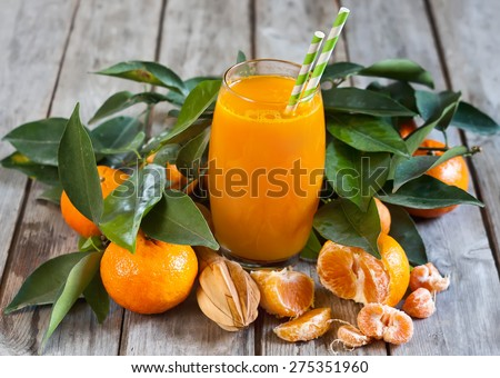 Glass of fresh tangerine juice with ripe tangerines, leaves and old-fashioned straws. - stock photo