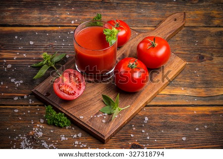Glass of fresh tomato juice and tomatoes on a wooden cutting board - stock photo