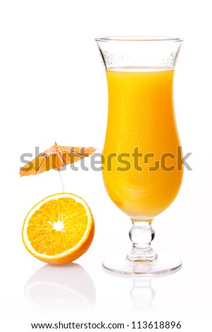 Glass of fresh tropical orange cocktail with a little party cocktail umbrella on a halved fruit on a reflective white studio background