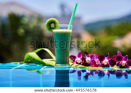 Glass of fresh tropical smoothie or kiwi juice and fresh kiwi on a wooden table and tropical background. Soft focus.