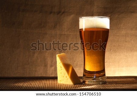 Glass of freshness beer with foam near cheese on gray canvas background - stock photo