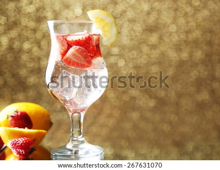 Glass of freshness lemonade with strawberries, on bright background
