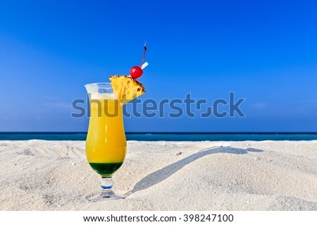 Glass of fruity cocktail is on a sandy beach - stock photo