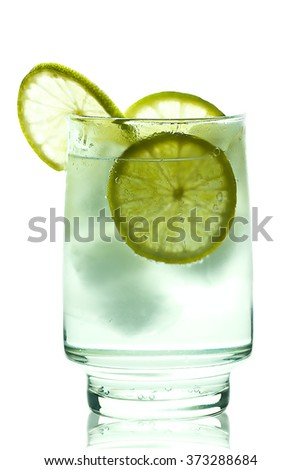 Glass of gin and tonic with ice cubes and lime slices - stock photo