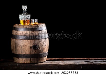 Glass of golden aged brandy or whiskey on the rocks - stock photo