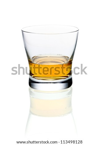 Glass of golden brandy or whisky on a white background with reflection