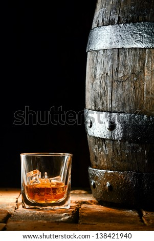 Glass of golden matured premium brandy or whiskey on the rocks alongside an old oak barrel standing upright on old bricks with a dark background - stock photo