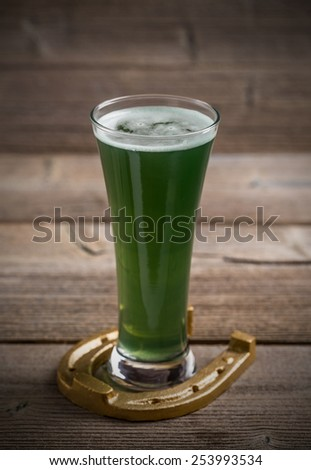 Glass of green beer and horseshoe for St Patricks day - stock photo