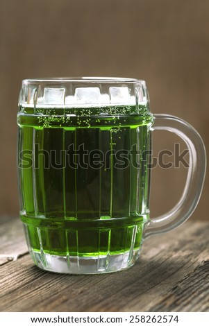 Glass of green beer for st. Patricks day on vintage wooden background - stock photo